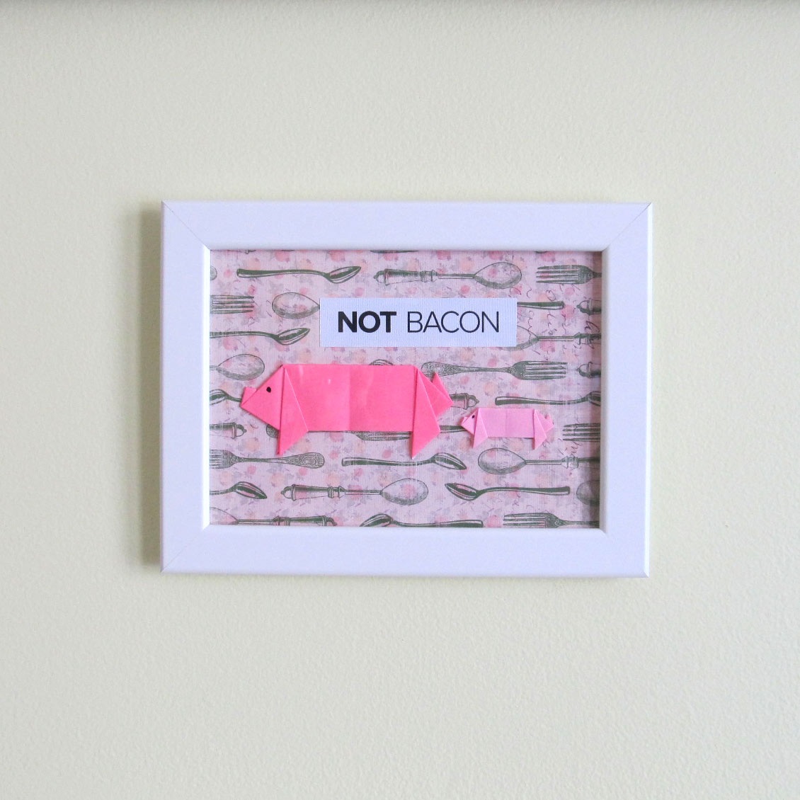 "Pink origami pig and piglet on vintage background with ""Not Bacon"" phrase"